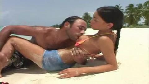 Une jeune brune transperc�e par un inconnu au bord d'une plage